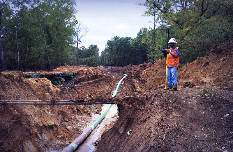 Man surveying land for pipeline installation
